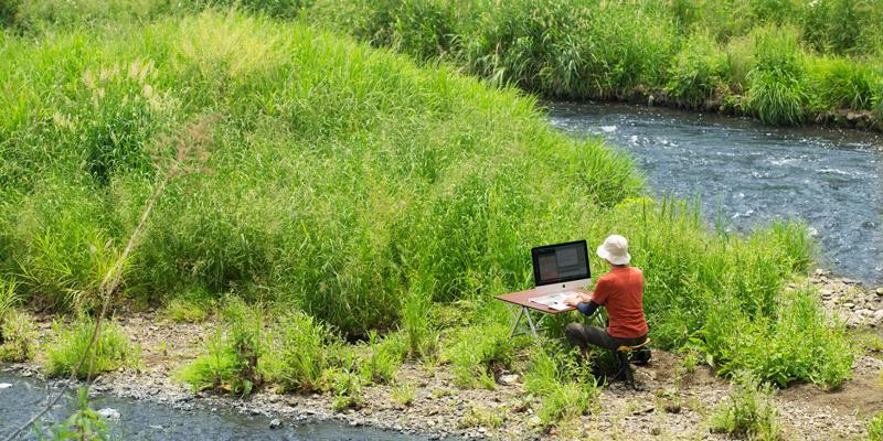 川の流れにたたずむ男性