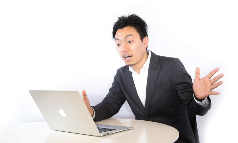 パソコンをみて驚く男性