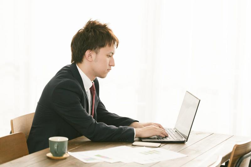 パソコンで求人情報をチェックするスーツの男性